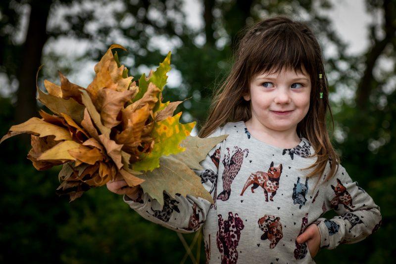 Petite fille avec des feuilles de platane