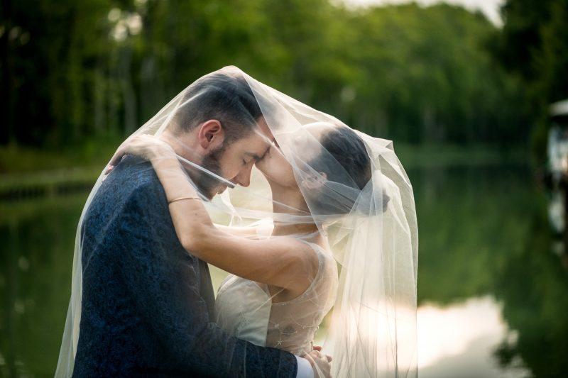 la mariée embrasse le marié sous le voile