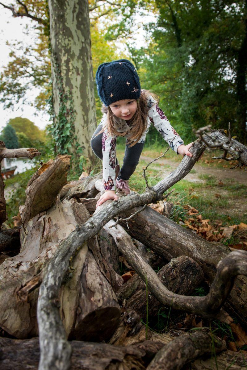 petite fille jouant sur des bois flottés