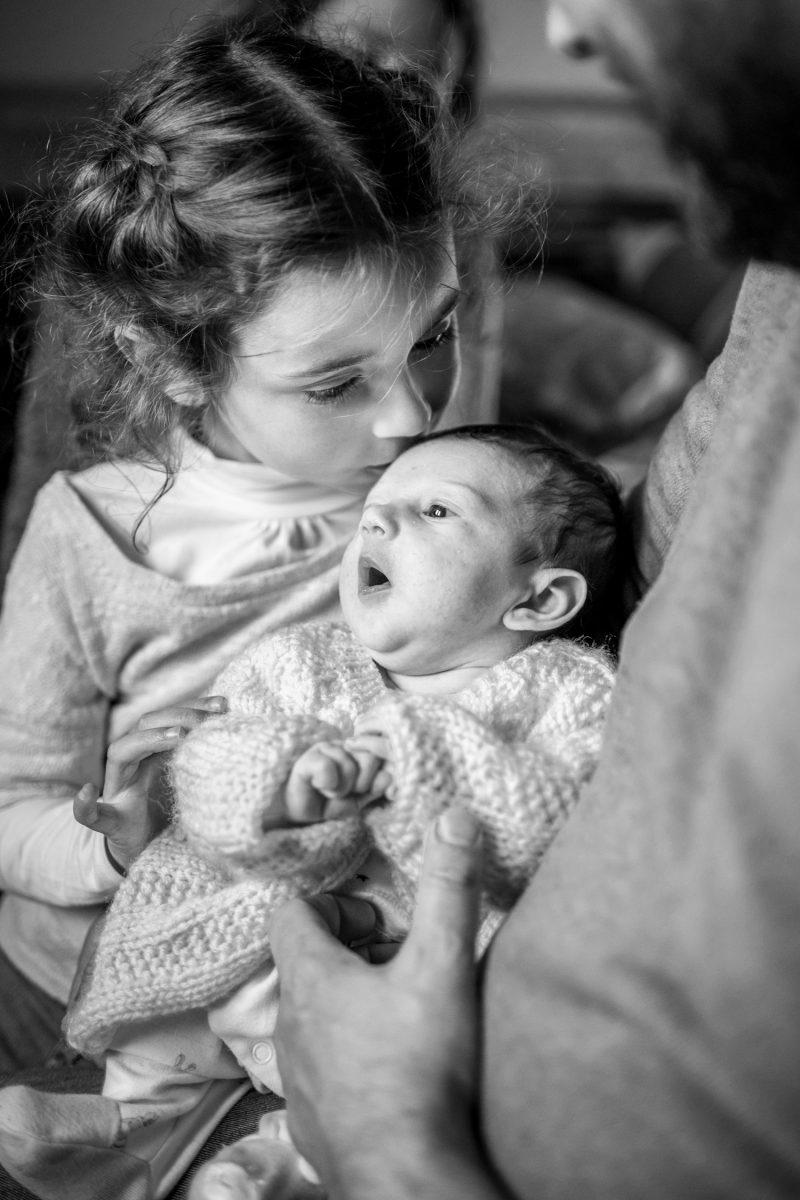 une petite fille embrasse son bébé