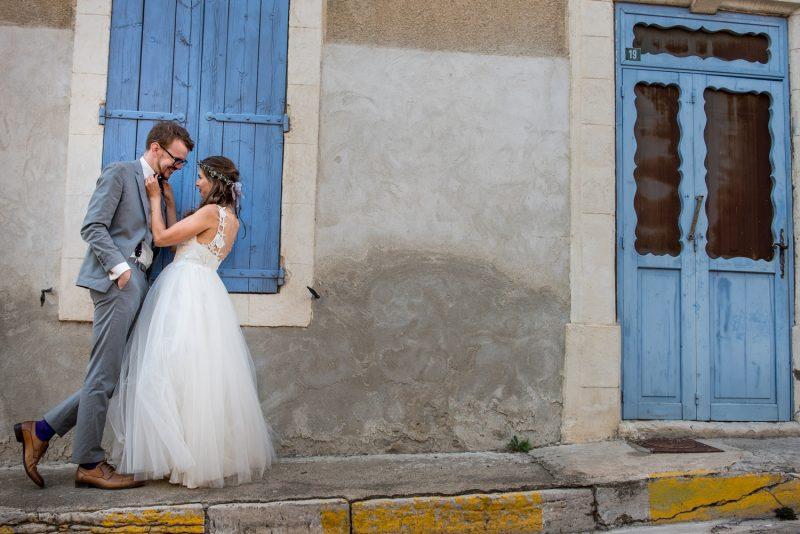 mariés devant des volets bleus