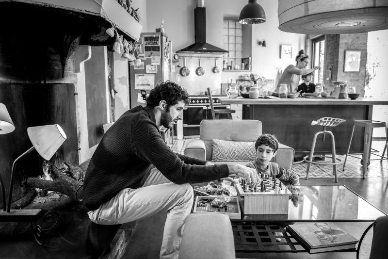 le papa et son fils jouent aux échecs